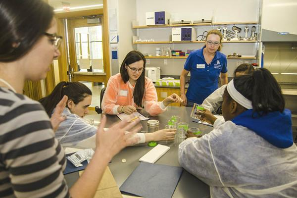 Middle school girls conduct an experiment under the watchful eye of Carmen Agouridis.