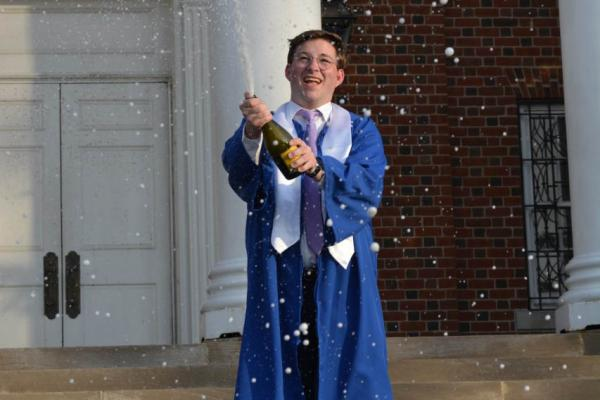 Zachary Chaney in graduation cap and gown popping a bottle of champagne on the steps of UK's Memorial Hall.