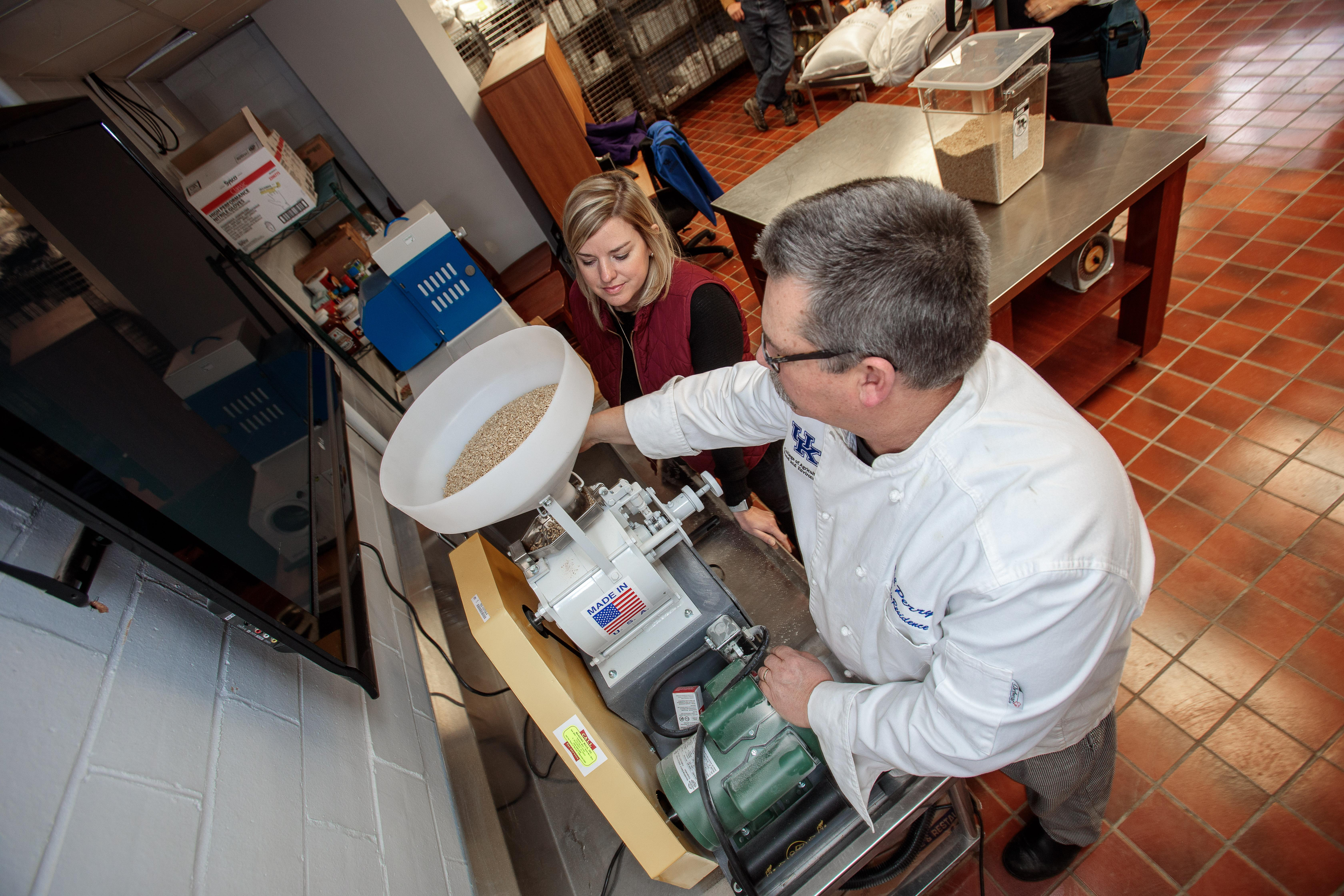 Sarah Halcomb watches as UK chef Bob Perry grinds some of her family's Edison wheat for use in the Lemon Tree, UK's student-run restaurant. Photo by Matt Barton, UK Agricultural Communications.