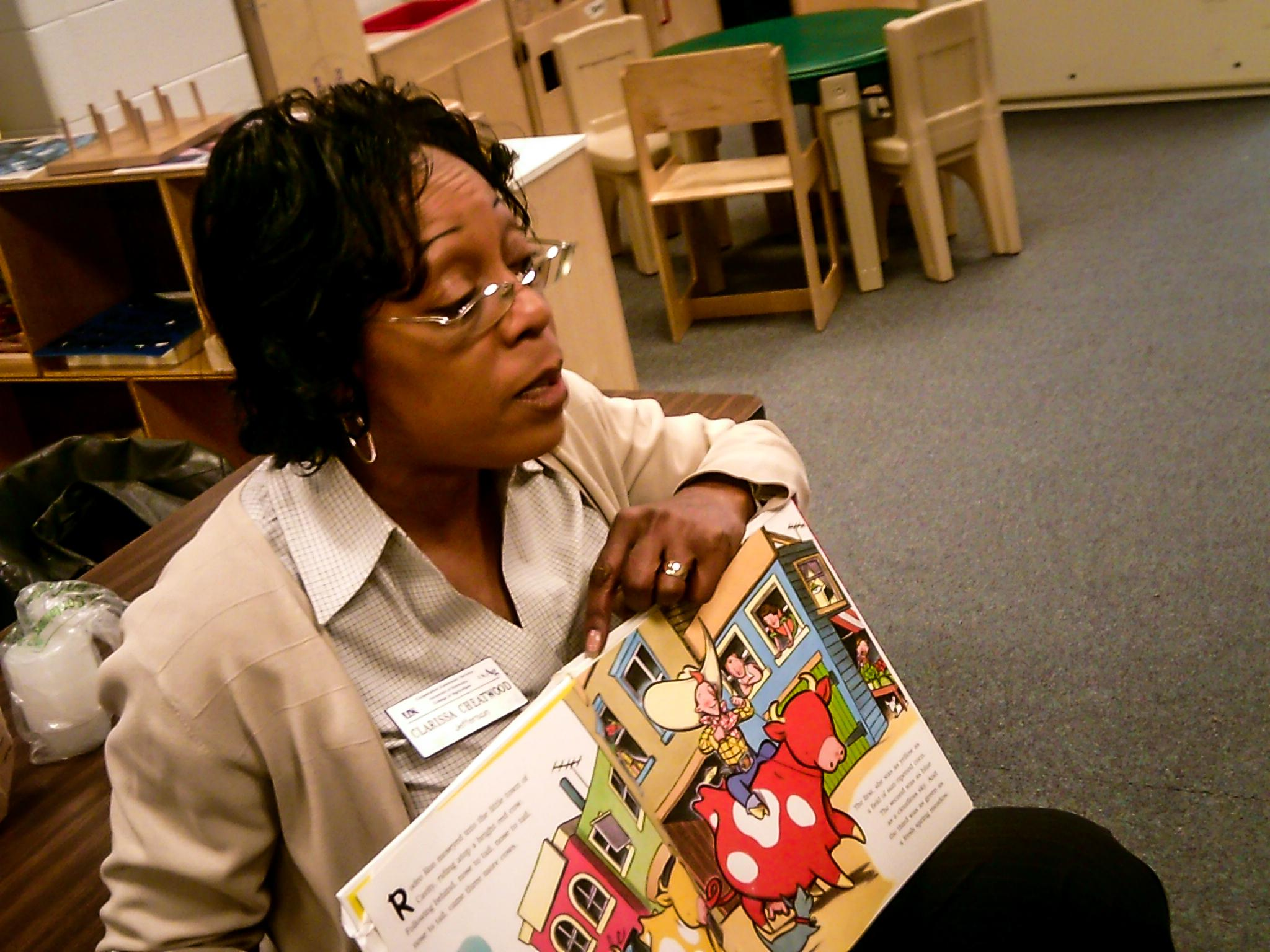 Jefferson County EFNEP assistant Clarissa Cheatwood reads to student at McFerran Preparatory Academy.