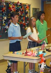 Students conduct a formal 4-H business meeting before finishing 1,000 paper cranes.