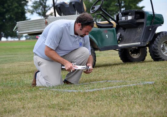 UK doctoral student Kenneth Cropper takes measurements in one of the lawn management systems at UK Spindletop Research Farm.