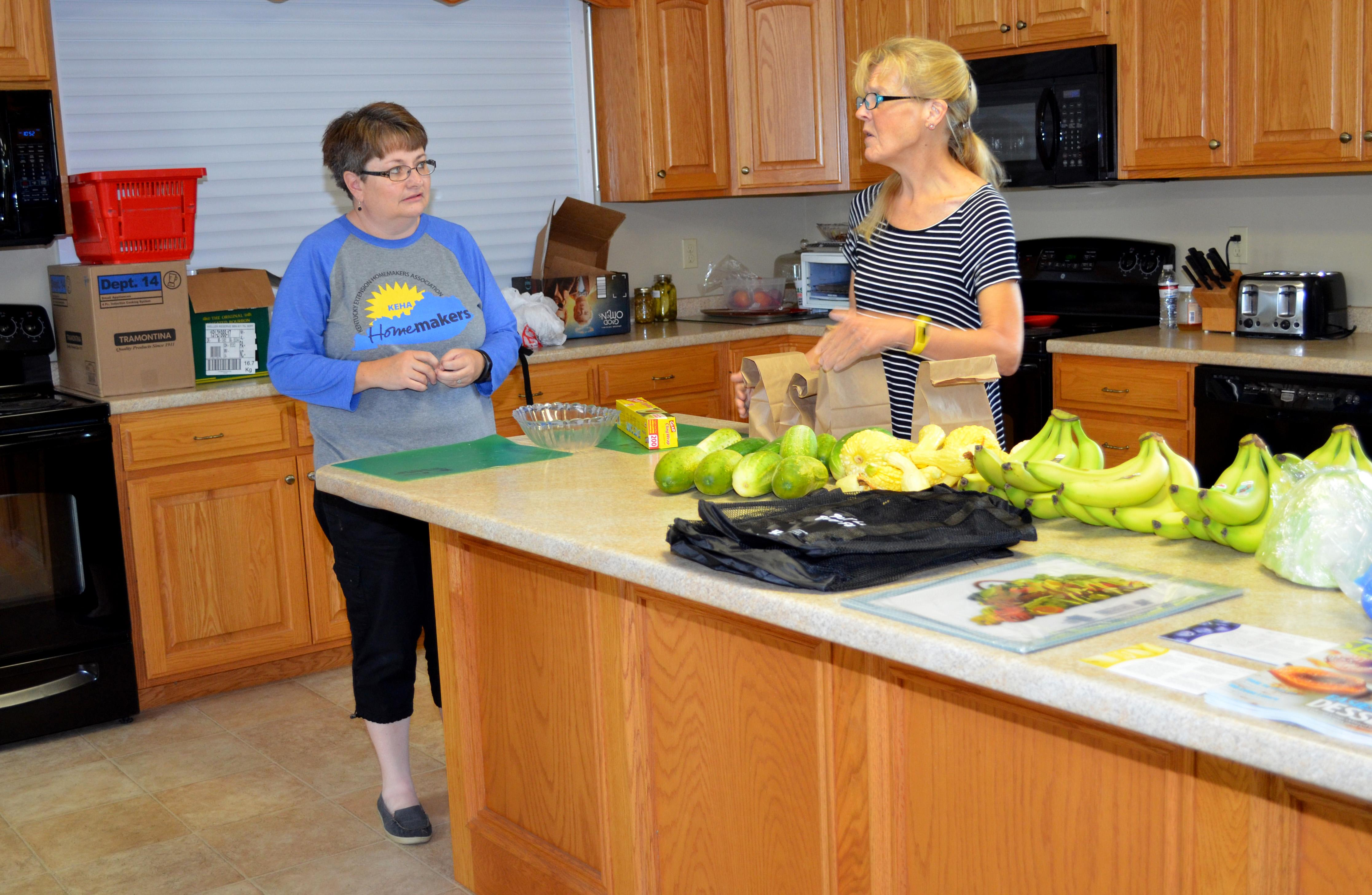 Debbie Messenger, left, Cumberland County family and consumer sciences extension agent, and Extension Homemaker Cathy Slowik sort  fresh produce for recipients of their summer feeding program. Photo by Katie Pratt, UK agricultural communications.
