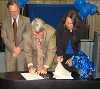 UK President Lee T. Todd Jr. (left) looks on as Agriculture Dean M. Scott Smith and Dentistry Dean Sharon P. Turner sign a memorandum of agreement.
