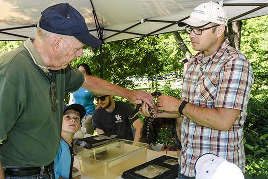 UK Forestry's Steven Price (r) shows off a snake at the Robinson Forest Field Day.