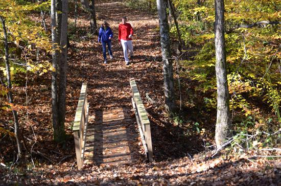 Local business owners Kerri and Al Barman walk along the nature trail they designed and cleared.