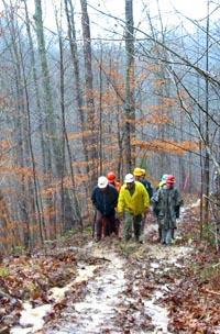 Foresters make their way up a muddy skid trail to the demonstration area.