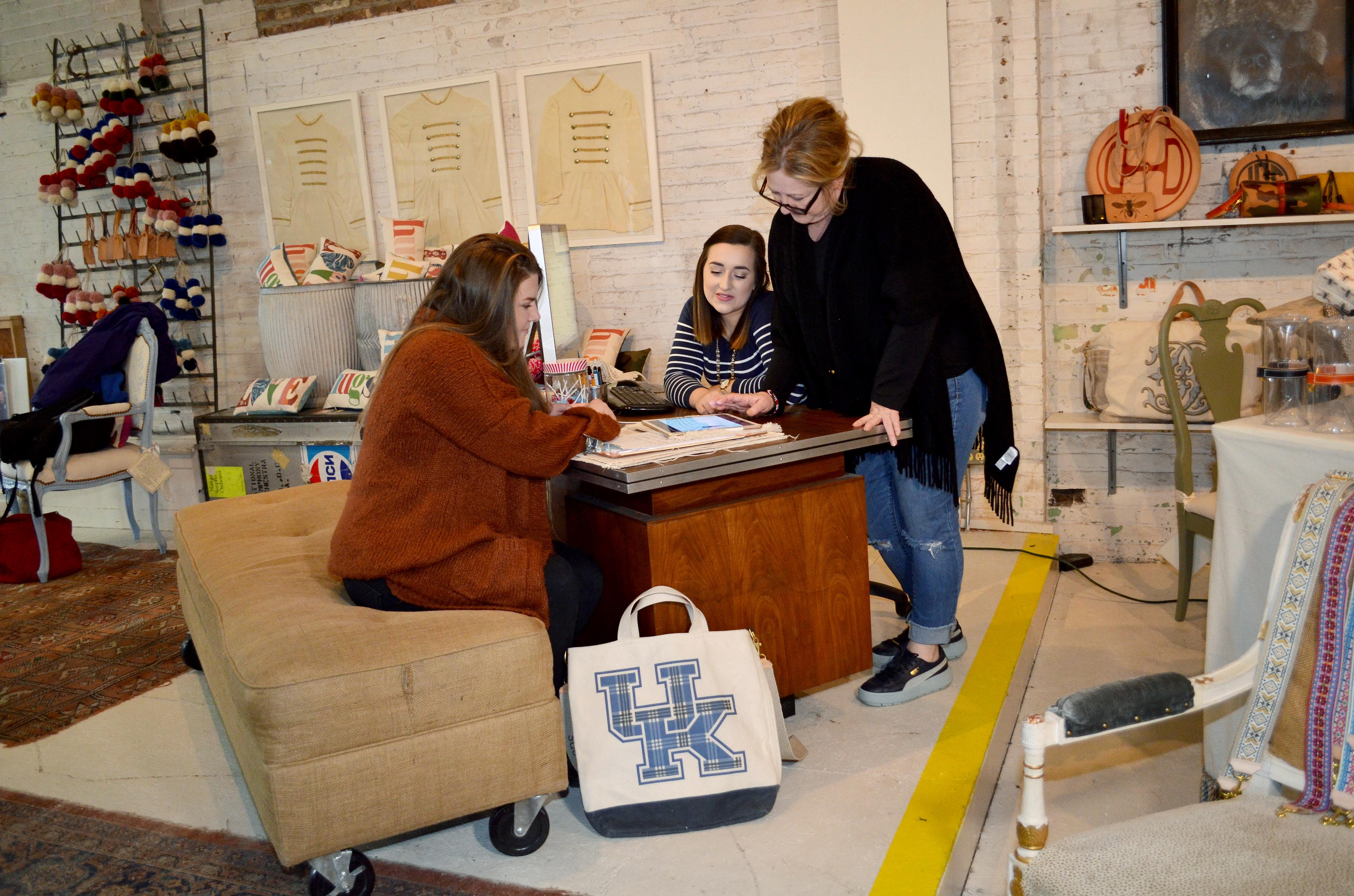 UK students Megan Stevenson, left, and Emily Stugan, center, look at Henry Dry Goods social media analytics with company owner Sherri Henry Wolf. Photo by Katie Pratt, UK agricultural communications.