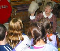 Students looking at teacher with raw wool