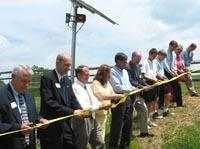 Officials cut a ribbon to signify the beginning of solar power at the Environmental Education Center.