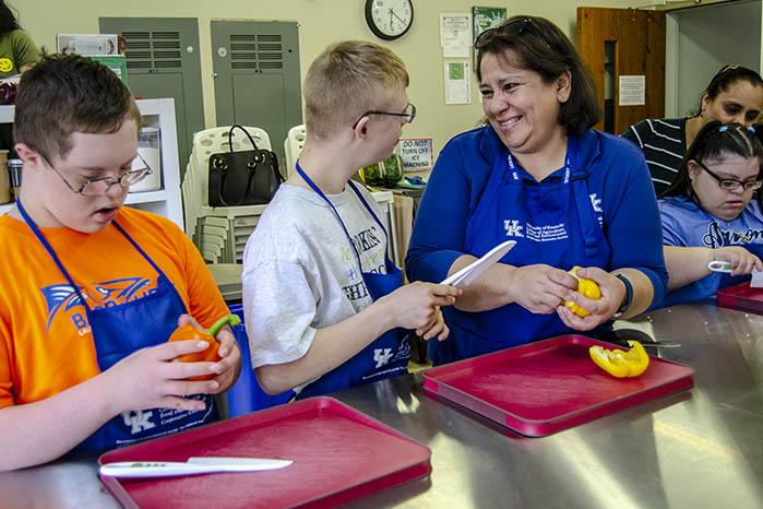 (l-r) Ethan Bourne, Sam Elbert, Jacqui Denegri, Maria Rosales, with her mother Francisca Rosales. Denegri shows participants in Fayette County Extension's Teen Cuisine class how to chop bell peppers.