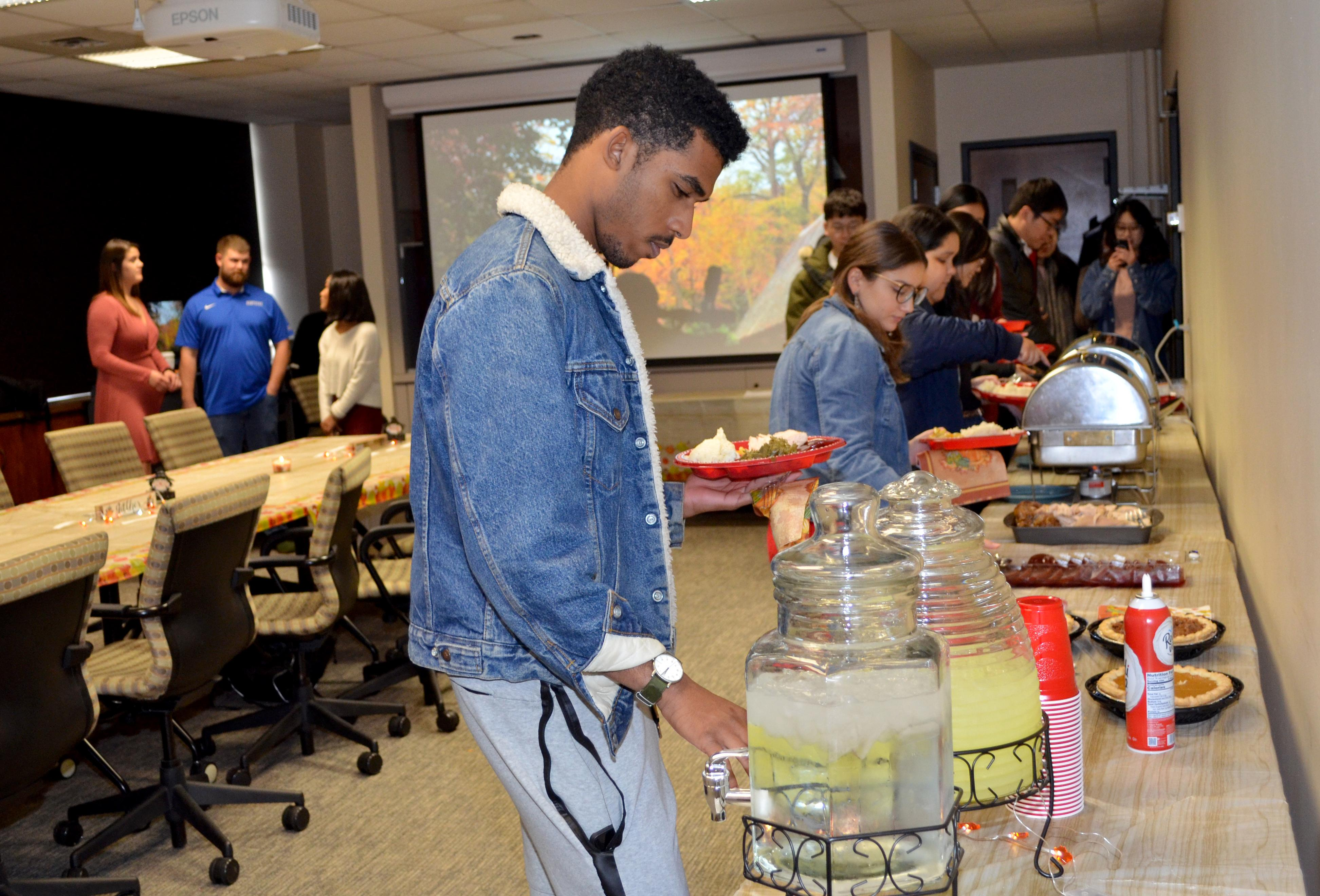 UK junior Ahmed Hamad pours some lemonade while making his way through the Thanksgiving buffet hosted by fellow UK students. Photo by Katie Pratt, UK agricultural communications.