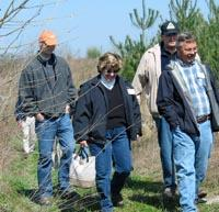 Tour participants walk through trees planted on uncompacted soil.