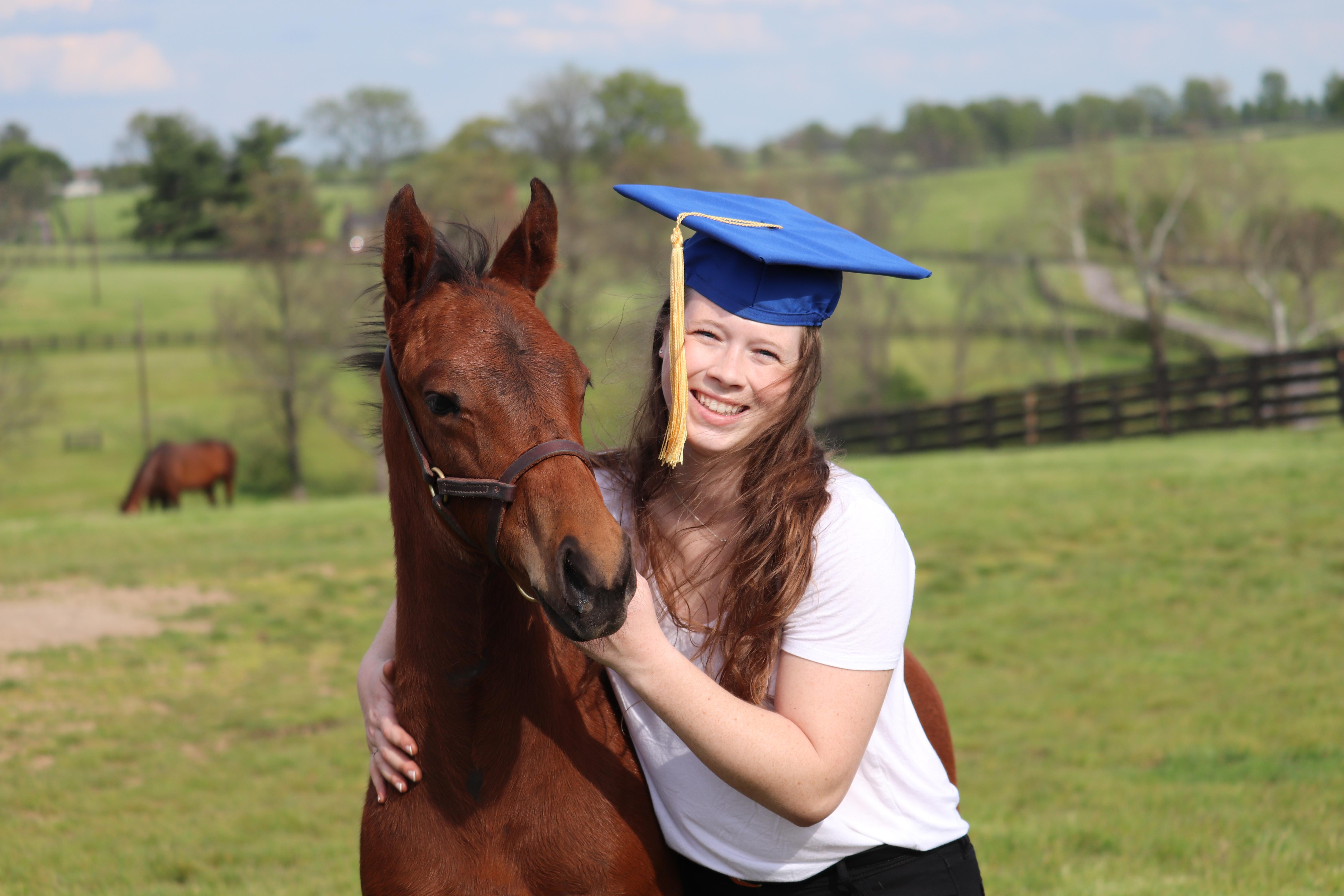 Hannah Moriarty in graduation cap, standing next to horse.