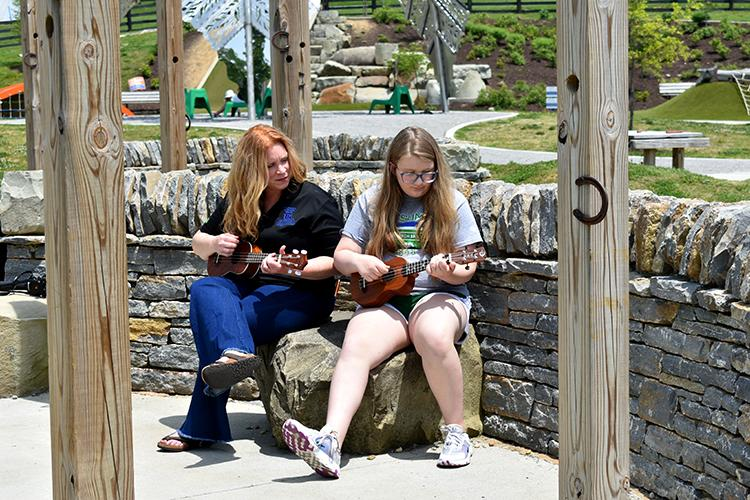 Jennifer Tackett, left, and Clark County 4-H'er Myla Leger, right, practice the songs Leger learned during the Virtual 4-H Ukulele Club at Legacy Grove Park in Winchester. Photo by Katie Pratt, UK agricultural communications.