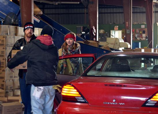 Cabrina Buckman, center, holds open a door for Alan Stubbs and another community volunteer as they fill cars with food.